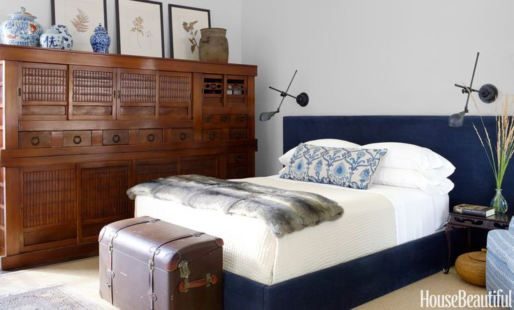 """In a Sonoma house decorated by Rela Gleason, the master bedroom was designed around the antique mizuya chest, with its bold iron hardware. A vintage """"boot"""" trunk from an old English automobile stands at the foot of a contemporary bed upholstered in indigo chenille. Bed linens by Garnet Hill. Wall lights by Restoration Hardware.   - HouseBeautiful.com"""