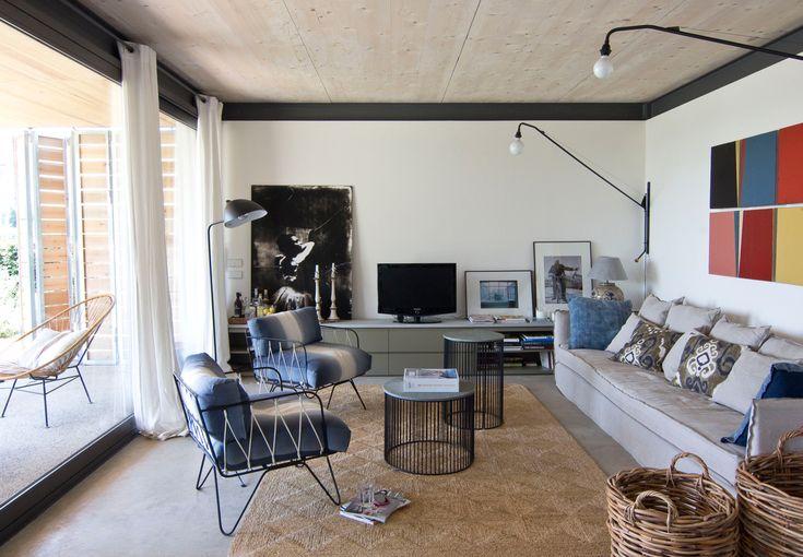 Salón con sofás oscuros, cuadros de colores, butacas y mesitas redondas