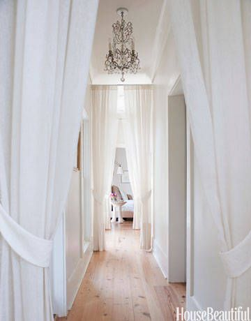 Creating their home at Serenbe — a Georgia utopian community — Marie and Steve Nygren wanted a warm yet minimal design. Designer Smith Hanes turned a negative in the home into a fresh, beautiful positive: he broke up the long hallway leading to the master suite by adding a row of white portieres. Amy Neunsinger  - HouseBeautiful.com