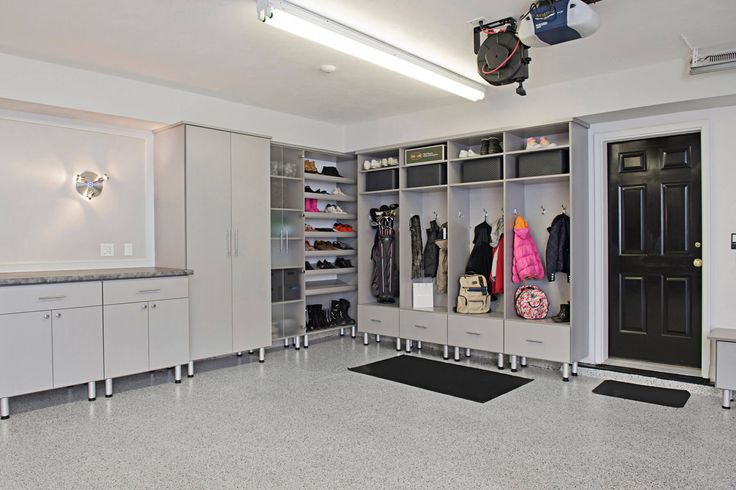 There's plenty of storage space for the entire family in this garage filled with tall cabinets with Lucite doors. A mudroom corner gives a neat finish for the overall room.