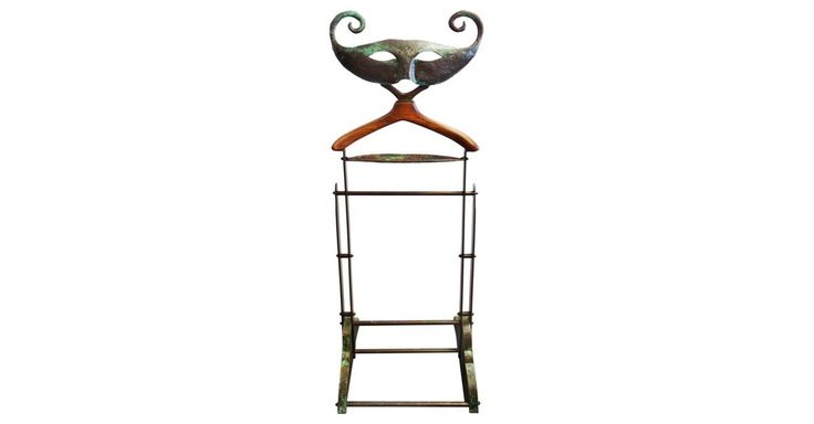 Sculptural hammered copper stylized Venetian mask clothes valet. The copper has a rich patina with verdigris accents. A copper tray is beneath the wood hanger. The base is clad in copper.