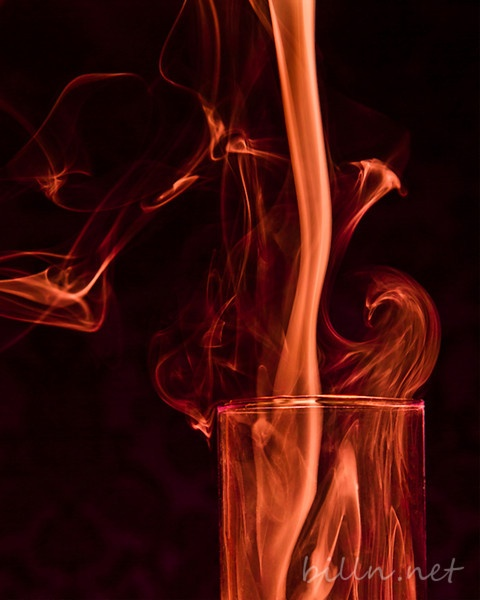 A photo of chilled smoke, descending into a narrow glass vase. The resurging smoke, as it warms, formed a loop of smoke that presents itself to my eye as a Phoenix, rising from the tube as if born of alchemical forces.