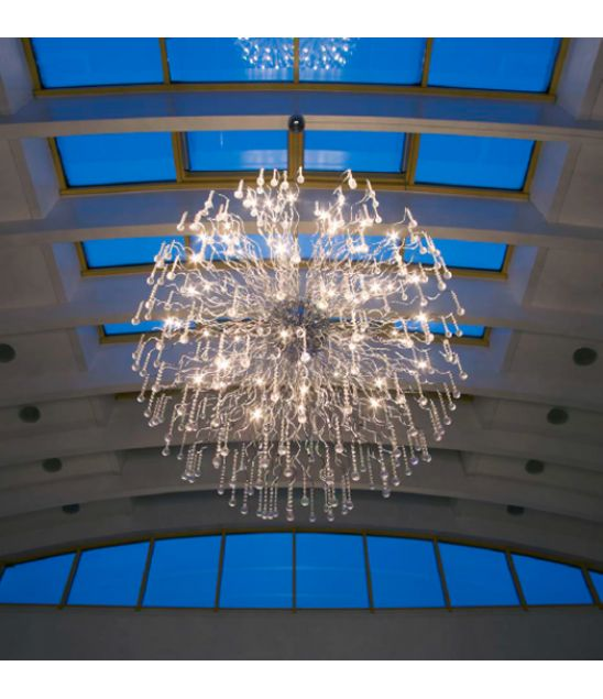 Nash Xxl  Denne lampen har store mål og sørger for glitrende lyseffekter i større rom. De bærende elementene har utallige bølgelinjer i krom og glasselementer i krystallform som tiltrekker seg oppmerksomheten. Denne store lampen ville komme til sin rett i en stor hall, et kjøpesenter eller på et annet offentlig sted. Den gjør inntrykk.Med elektronisk transformator.