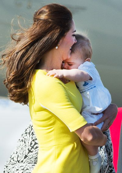 Feeling a tad camera shy, Prince George takes a moment to cuddle in his mother's arms before greeting those awaiting his family on the tarmac.