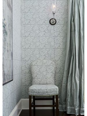 For English charm, Smith covered walls in Bennison's Roses in Mono Grey/Oyster floral linen and used the same print on the armless chairs.