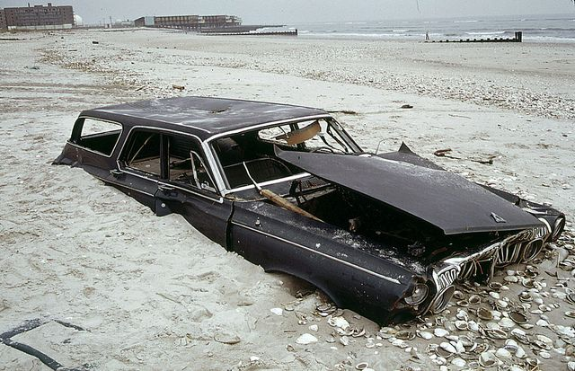 Welcome to New York, 1973 style! Half buried early 1960s Dodge Polara station wagon on the beach at the ocean side of Breezy Point in Queens. Abandoned apartment building at left distance.