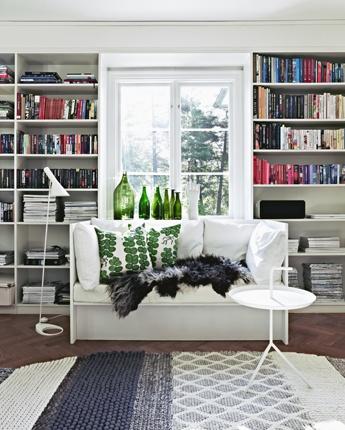 Jonas Ingestedt. Bookshelves around the window; white and green sofa. Josef Frank cushions from Svenskt Tenn cushions and Arne Jacobsen light.