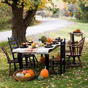 Really cute and festive outdoor Halloween party with pumpkins piled around and a mix of chairs