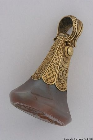 Watch Fob, ca.1890. engraved agate and gold. Fobs dangle from the end of a gentleman's watch chain visible on his waistcoat. While decorative this is also a seal.