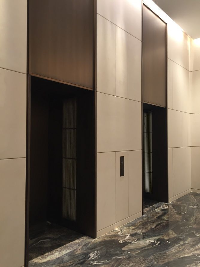 exaggerated lift head; full height effect; simple grid paneling; ivory, bronze, grey palette [Park Hyatt Hotel Hangzhou]