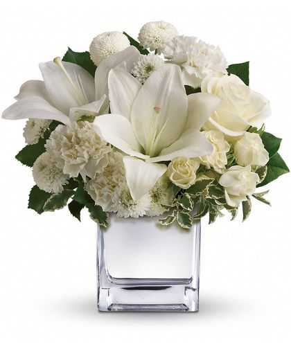 Surprise a faraway friend with this elegant array of Christmas flowers. White roses, lilies and other favorites are displayed in a clear cube. Simple and affordable, it is a lovely gift that will brighten spirits without breaking your bank. #kityysflowers