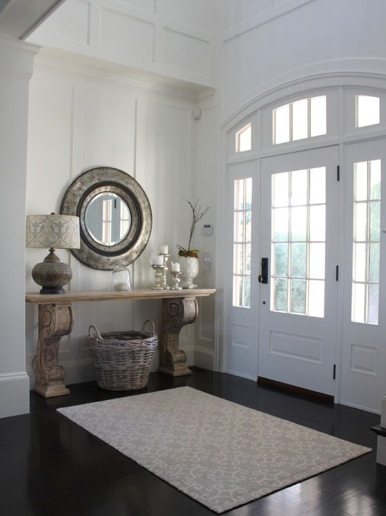 Molly Frey Design | Beach Style Front Entry | Dark Flooring White Paneled Walls | Statement entry table made with large corbels as legs and rattan basket for storage accented with round mirror.