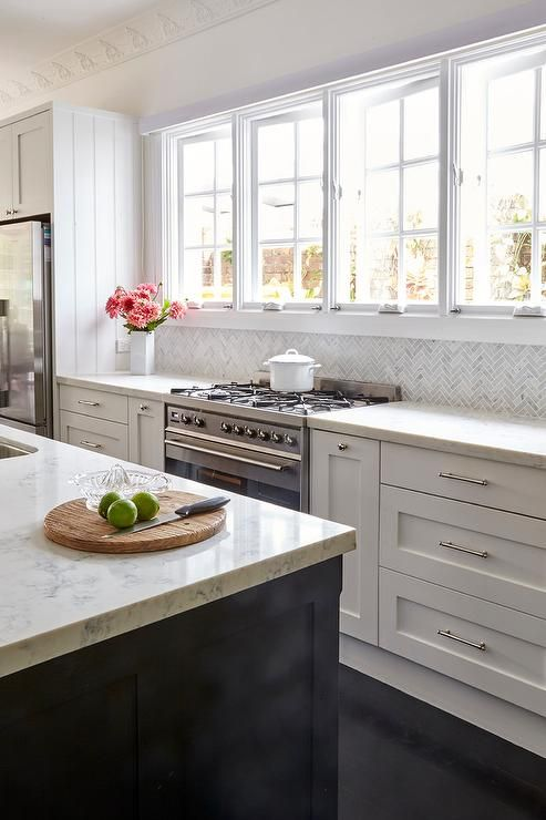 A row of windows are fixed above a stainless steel oven range flanked by white shaker cabinets donning polished nickel hardware and a white quartz countertop lined with gray marble herringbone backsplash tiles as a stainless steel double door fridge sits enclosed beneath white cabinets mounted against a white wall lined with ornate crown molding.