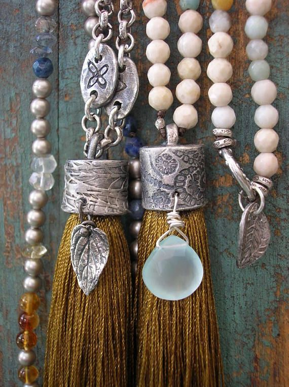 A lush golden tassel is topped with my handcrafted fine silver (99% pure silver) tassel cap. Embellished with a sparkling aqua chalcedony gem, it swings from a breezy strand of petite faceted gemstones in soothing colors of cream, aqua, clay and brown. Sterling silver ring with a fine silver leaf dangle brings everything together at the back of your neck....*so* easy to wear, just slip it over your head and go! *ULTRA* long at 36 inches. The tassel pendant adds approximately 4 inches. One…