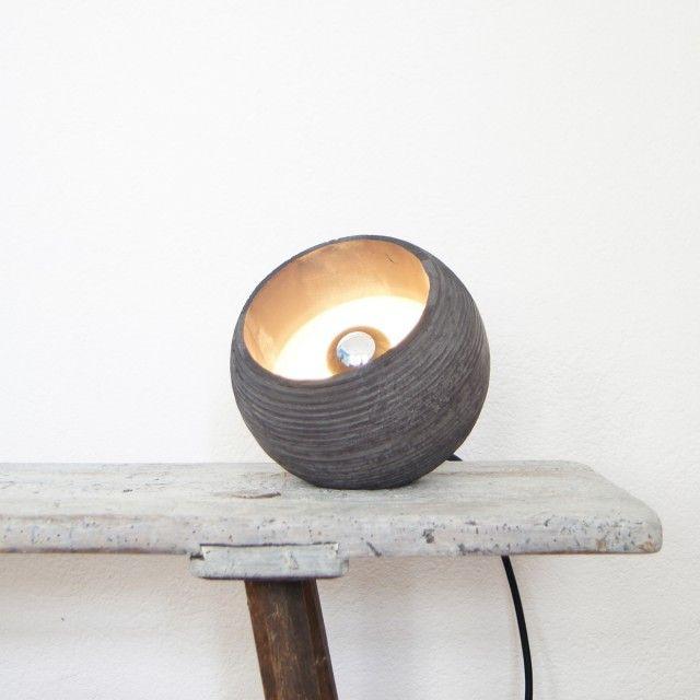 Betonleuchte aus rohem Beton. Diverse Farbvarianten sind durch Pigmentierungen möglich. Die weiße Variante wird aus feinem, weißem Spezialbeton gegossen.Die Lampe ist eine abgestufte, fast geschlossene Kugel. Das Licht tritt durch die untere Öffnung heraus.Eine Abflachung, schräg an der Oberseite, macht es möglich, dass man sie auch hinstellen kann.Die Lampe wird mit einer goldenen Metallfassung und einem Textilkabel geliefert. Die stehende Variante hat einen Schalter und einen Stecker.Jede…