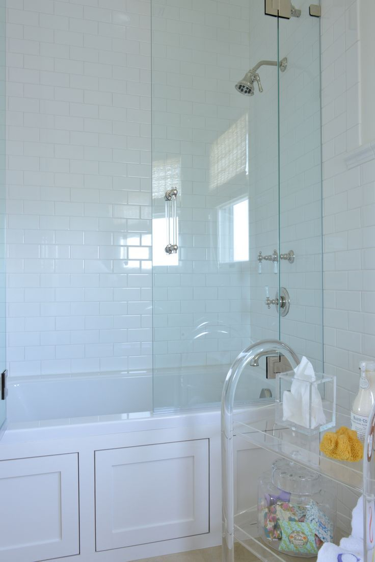 1320 best bathroom envy images on pinterest bathroom ideas chic bathroom features a wainscoted drop in tub with a seamless glass shower partition filled with subway tile surround situated next to a lucite bath cart