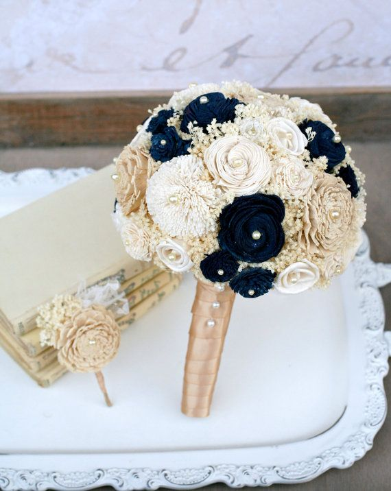 This custom handmade gold & navy bridal bouquet features sola wood mums dyed in a gorgeous gold wash that shimmers softly in sunlight. Rich navy blue assorted sola flowers, neutral ivory cream sola wood flowers, dainty handmade ivory lace flowers, bleached ivory dried babys breath, and cream pearl accents complete the flower bouquet. If your wedding colors are gold and navy, you will love this chic bridal bouquet.  This is a medium sized brides wedding bouquet. Measures about 10 inches ...