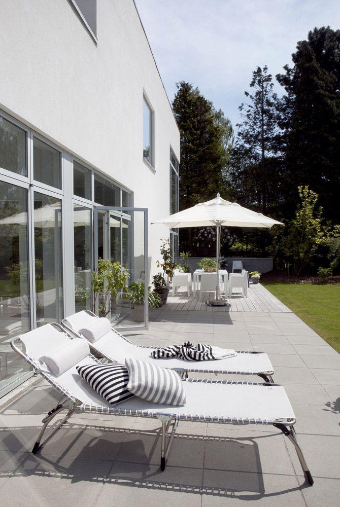 Liggestolene, Amigo fra Fiam  kan tåle at stå ude hele året. De er købt hos Svendsen & Søn i Gilleleje. De stribede puder og plaiden er fra Louise Roe, imens havemøblerne ved parasollen er designet af Philippe Starck for Driade.