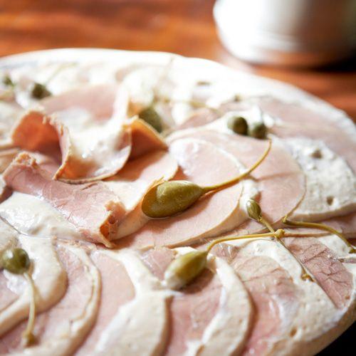 Italianen gebruiken girello, schoudermuis, want die geeft dwars op de draad gesneden fijne plakjes met een dichte textuur. Gebraden varkenslende is een goed alternatief.