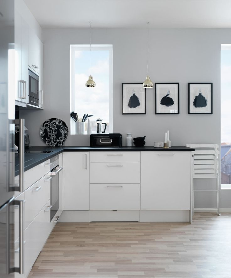 The artwork and delicate golden pendant lights add an air of elegance and sophistication to this kitchen from Sigdal kjøkken in Norway.