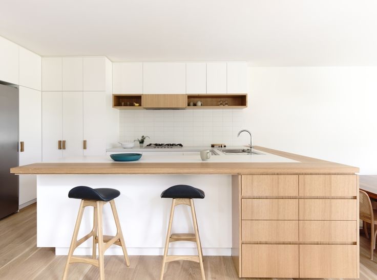 In the kitchen, black-cushioned bar stools by Erik Buch pop against the blonde wood counters, custom white melamine cupboards, and milky ceramic tile backsplash. The kitchen sink is by Franke, the faucet by Grohe, and the fridge by Liebherr.