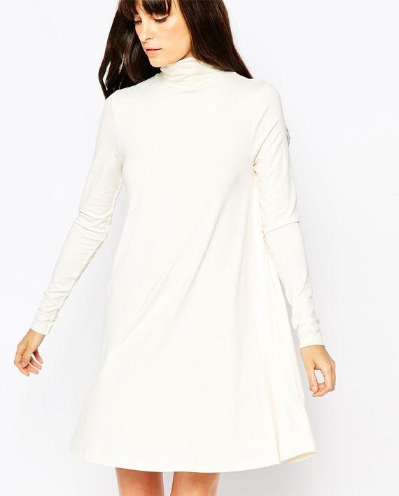 Romantisk-chic kjole med med polo hals og lange ermer i hvitt. Kjolen når like over kneet. Ideell for denne sesongen. Kombiner gjerne med en oversized skjerf og støvler.