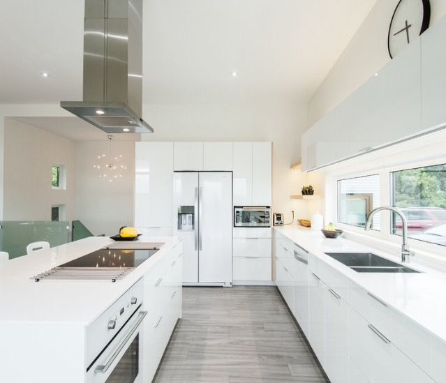 Sleek White Kitchen with beautiful White and Silver appliances.