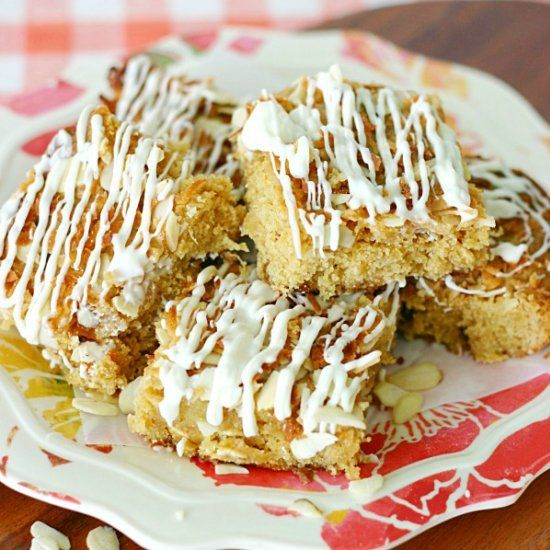 Chewy White Chocolate Pineapple Coconut Cookie bars topped with crunchy coconut, sliced almonds, and white chocolate.