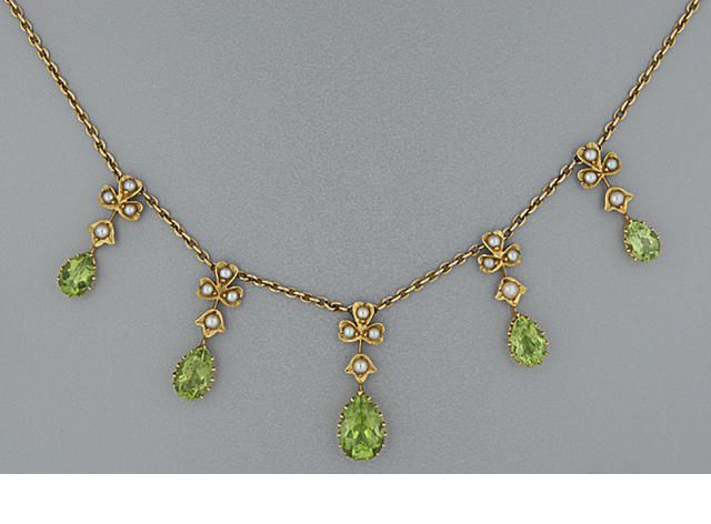 An Edwardian peridot and pearl necklace Composed of a fringe of five graduated pear-shaped peridots with clover-leaf pearl surmounts, on a trace chain, length 40.0cm.