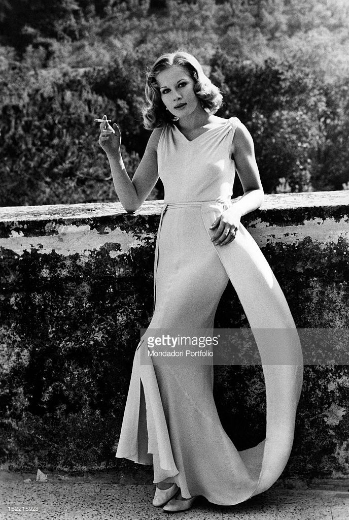 Dominique Sanda, who plays the role of Micol in Il Giardino dei Finzi Contini based on Giorgio Bassani's novel, is posing: she's very elegant and is smoking a cigarette leaning against a wall. Frascati, 1970