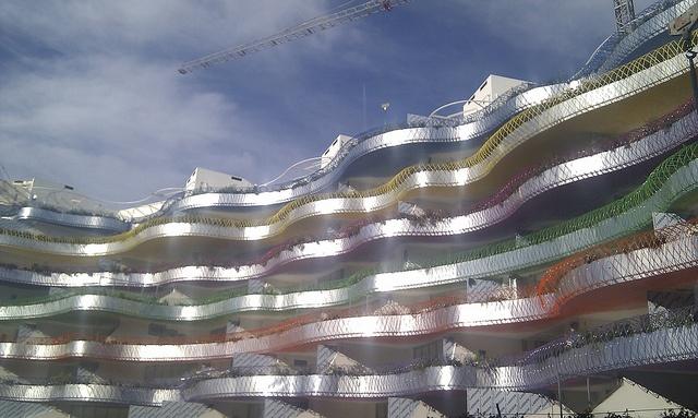 Cerramientos exteriores de dos edificios formados por dos tipos de carpintería.  En el edificio A balconera deslizante de aluminio incoloro con barniz protector colocada sobre premarco de base.  En el edificio B la carpintería es de aluminio con rotura de puente térmico en acabado lacado blanco, tipo oscilobatiente o fijo, colocado sobre premarco de base.