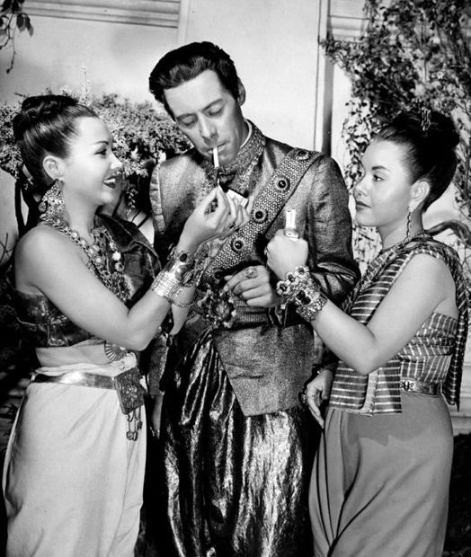 Rex Harrison stops for a cigarette while filming Anna and the King of Siam