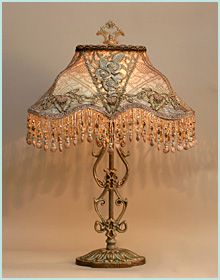 Decorative antique lamp base has been hand-painted and holds a hand-dyed Edwardian silk lampshade. The shade is ombre-dyed from pale champagne pink into pale blue. The shade is covered on the sides with coppery-gold metallic lace and the front is overlaid with beautiful Edwardian (Titanic era) floral passementerie and silver metallic handmade antique ribbon roses. The shade has hand beaded fringe in matching tones.