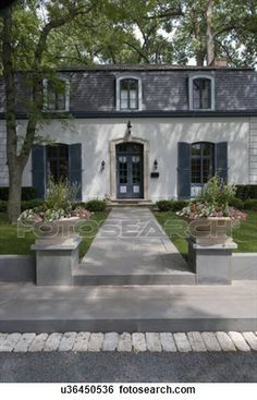 EXTERIORS: vertical of French country home, shutters, long windows, mansard roof, dormers, planters on pedestals sit on either side of walkway leading to front entry, steps with brick, gravel and stone View Large Photo Image