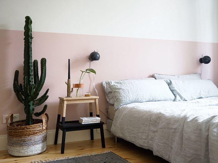 A forma rústica do grande cacto, colocado ao lado da mesinha de cabeceira, contrasta com a delicada faixa cor de rosa da parede.