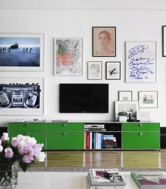 Different art styles come together beautifully and make the TV barely noticeable above the gorgeous green cabinet.