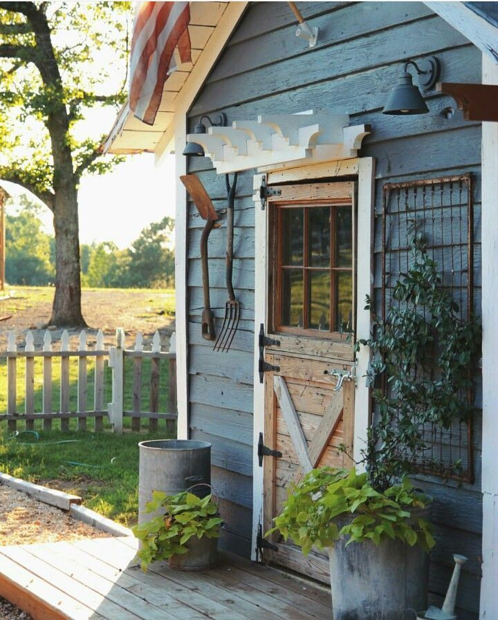Cute gray garden shed. Love the dutch door, galvanized planters and bed springs as a trellis.