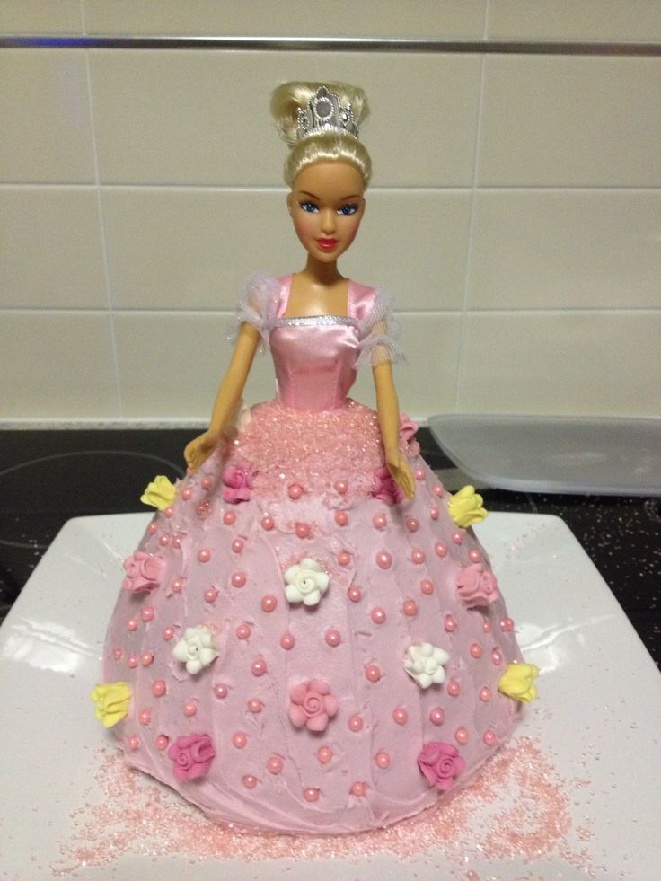 Dolly Varden tin butter cake. Betty Crocker pink icing, and a few packets of Supermarket decorations. $5 Barbie. I cannot bake, anyone can do this.