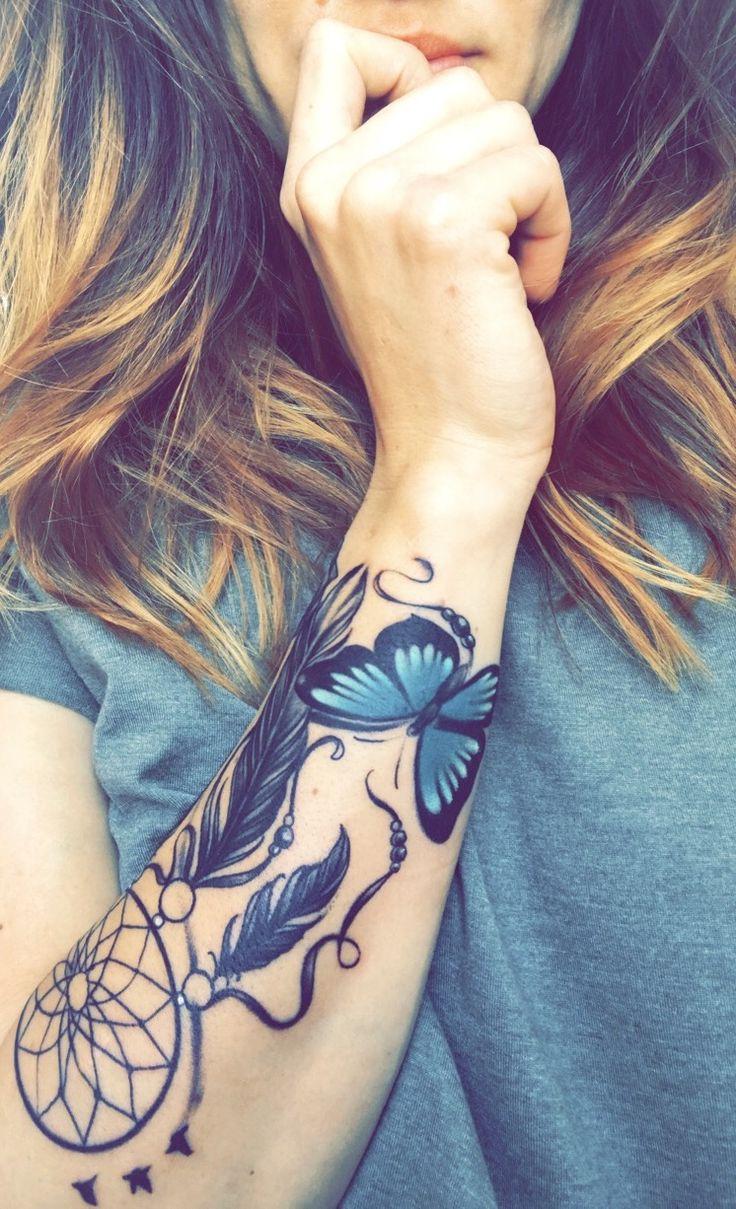 tatouage attrape reve graphique., cerceau filet et plumes noires et dessin papillon en noir et bleu, bras femme