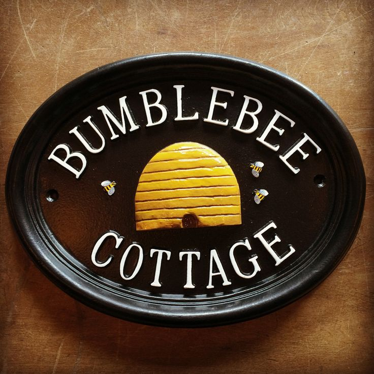 A pretty hand painted house sign with bumble bee and honey hive design.