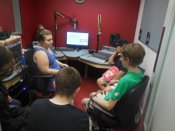 The participants are learning about radio equipment and how to use the microphone in a radio studio