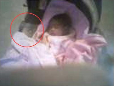 This baby was three weeks old and was resting comfortably in her car seat when the mother took a picture - After the picture was developed, she saw the gray image next to the baby that appeared to be another baby - The mother had lost her first baby due to a miscarriage and thinks that this was her lost baby coming to watch over her newborn sister.