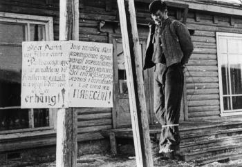 Encyclopédie EHNE, article : Combattre la résistance en Europe occupée, 1939-1945.  Exécution d'un partisan à Minsk, 1942-1943. Panneau, en russe et en allemand: «Voici le chef d'un groupe de guérilla. Il a tourmenté et pillé la population pendant des mois. Il est donc PENDU!».
