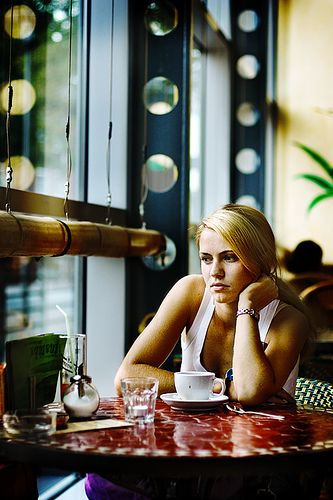 """Photographer : Joche Van Eden  Title: """"Light my Fire""""  a young woman waiting impatiently for her guest to arrive... finished her cup of coffee and looks frustrated. The coffee shop looks like an excellent place for her to let loose her frustration because the environment looks calm and soothing."""