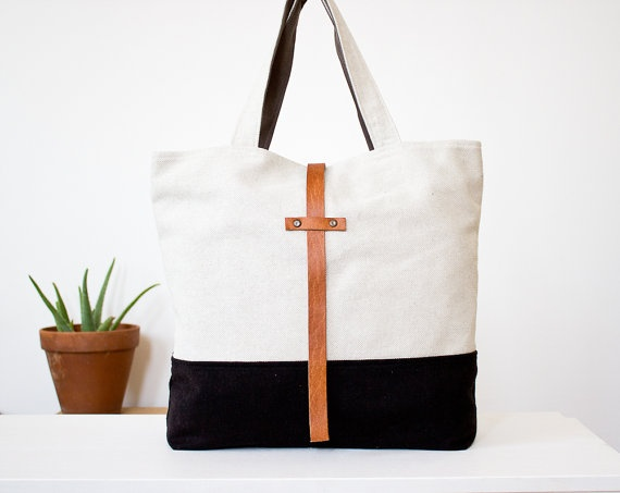 """cotton tote bag, wool base in black; closes with leather strap; grey cotton lining with inside 7""""x7"""" zippered pocket. The bottom of the bag has box pleats; interfacing for additional structure, double stitched seams.    DIMENSIONS:  Top width: 18.1""""  Bottom width: 14.6""""  Height: 15.4""""   Deep: 3.9""""  Strap: 19.3 inches"""