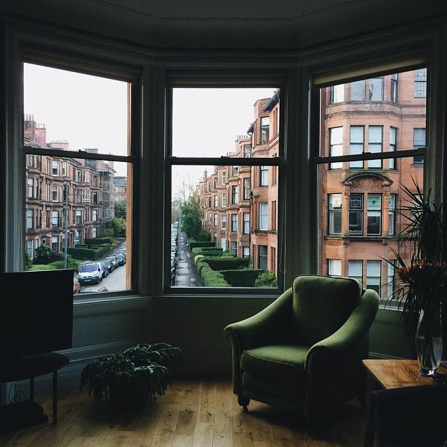 Introspective corner in a living room, with a dark greem armchair, and with a view to the neighborhood