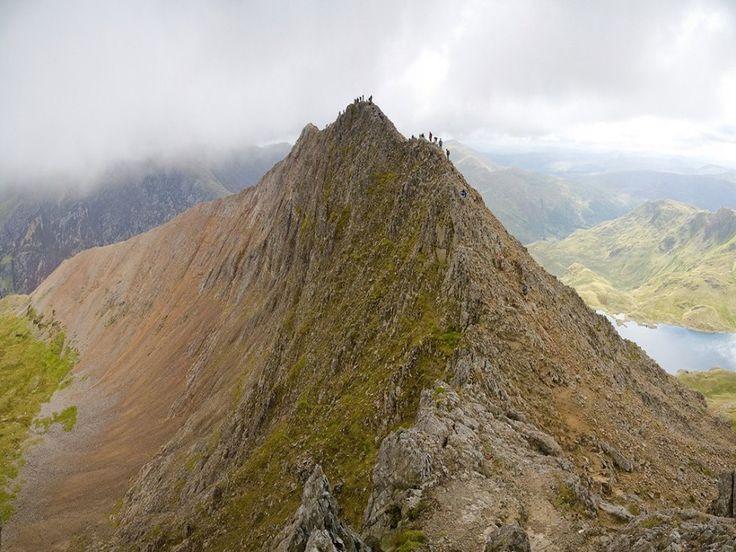 """Crib Goch (Parc national de Snowdonia, Pays de Galles) Le Crib Goch ou """"peigne rouge"""" en gallois, est un sommet du massif Snowdon constituant l'arête occidentale acérée du Garnedd Ugain et qui culmine à 923 mètres d'altitude.  Cette ascension est l'une des plus difficiles et périlleuses du coin, avec des arêtes de couteaux tranchants, qui peuvent même laisser les alpinistes les plus expérimentés sur le carreau."""