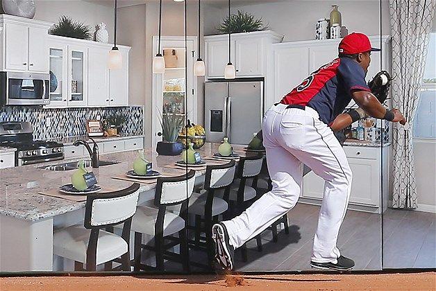 O jogador do Cleveland Indians Carlos Moncrief pega uma bola jogada por Kristopher Negron, do Cincinnati Reds, na parte direita do campo em um jogo de beisebol em Goodyear, Arizona. Quando olhamos rapidamente, parece que o jogadore está dentro de uma cozinha, mas na verdade trata-se de um anúncio