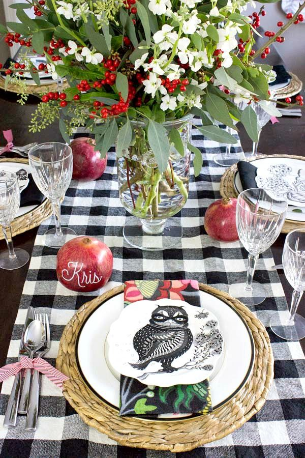 Holiday placesetting with floral centerpiece, pomegranate place cards, silverware tied with ribbon, buffalo check runner, and festive plates