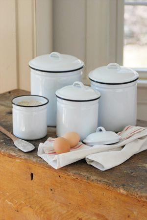 "White Enamelware Canister Set  set of four  Add a little vintage style to your farm kitchen or bath with this White Enamelware Canister Set. Set includes four white enamel canisters with black trim. Canisters are 4"", 5"", 6"" and 7"" (not including lid height). Food Safe.    Price: $52.95"